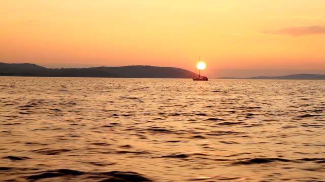 Sailboat sailing in the bay at sunset
