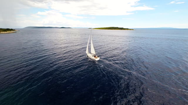 aerial sailboat sailing near the island - sailing boat stock videos and b-roll footage