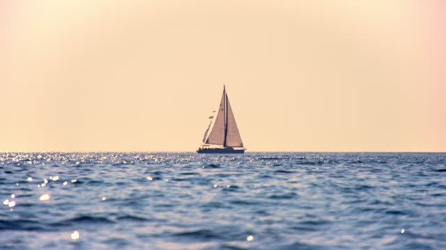 slo mo sailboat sailing on the horizon at sunset - sailing boat stock videos and b-roll footage