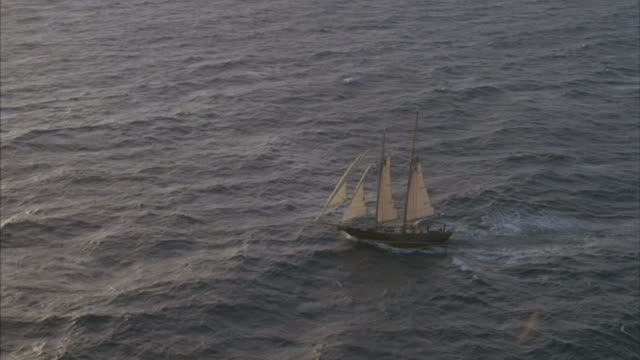 a sailboat sails through the rough ocean with all sails out. - small boat stock videos & royalty-free footage