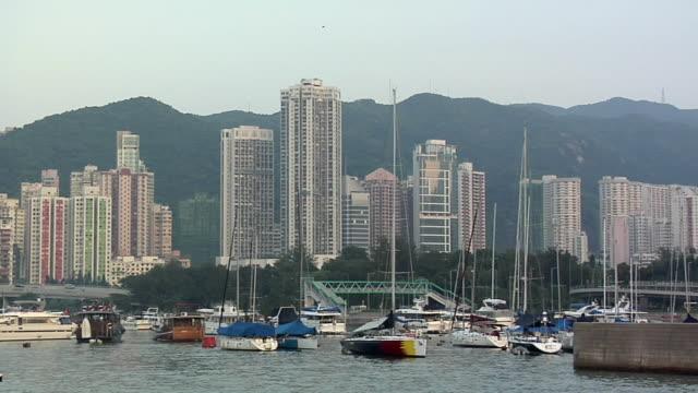 ws sailboats anchored in bay, causeway bay skyline in background / hong kong, china - anchored stock videos & royalty-free footage