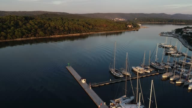 sailboats anchored on a pier in bay of an island in adriatic sea - anchored stock videos & royalty-free footage