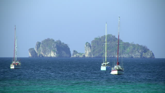 ws sailboats anchored on sea, cliffs in background, krabi, thailand - see other clips from this shoot 1459 stock videos and b-roll footage