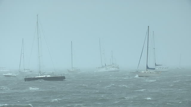 sailboats battened down for an impending storm bob around in the storm swell. - moor stock videos & royalty-free footage
