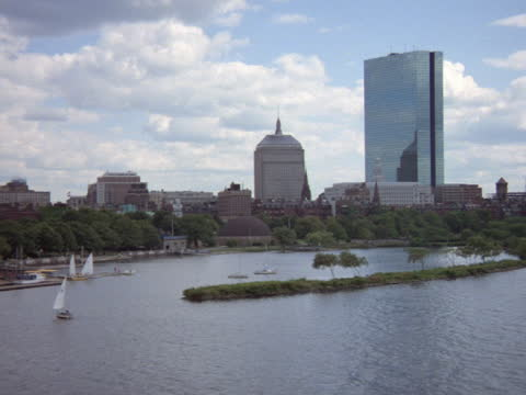 sailboats float in the charles river beside a skyscraper in boston. - boston massachusetts stock videos & royalty-free footage