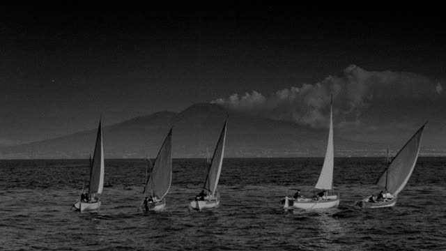sailboats glide near coastal mountains in 1942. - cumulus stock videos & royalty-free footage