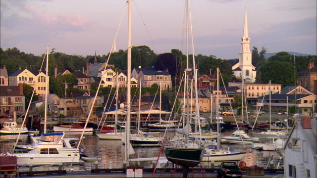 MS, sailboats in harbor at sunrise, town in background, Camden, Maine, USA