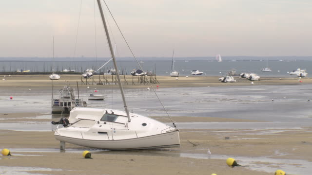 sailboats lie on a beach when the tide is out - cap ferret stock videos & royalty-free footage