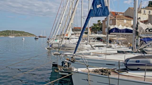 4k segelboote liegeplatz im sonnigen marina, real-time - vertäut stock-videos und b-roll-filmmaterial