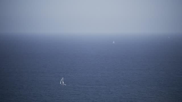 Sailboats on blue ocean, hazy blue skies