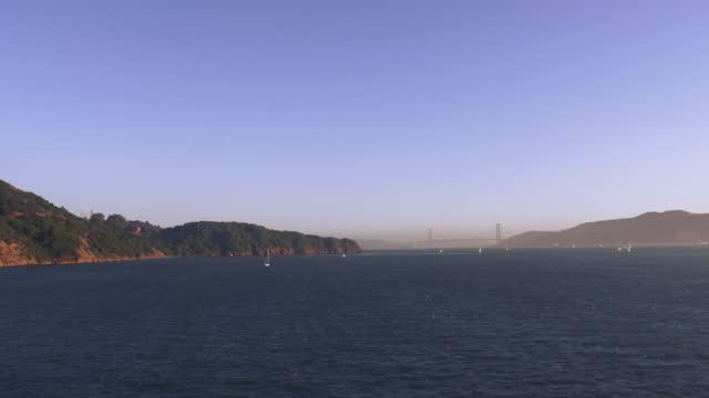 vídeos de stock e filmes b-roll de sailboats on the water with golden gate bridge in the distance; mist forming in the distance - baía de são francisco