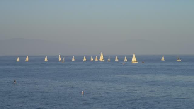 Sailboats sail on the Pacific Ocean near the marina at Santa Barbara, California