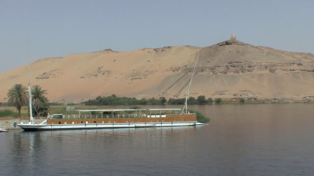 POV Sailing along Nile riverbank with feluccas, tombs of the nobles and Dome of Wind in background, near Elephantine Island, Aswan, Egypt