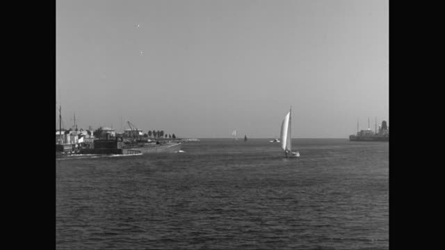 WS Sailing boat and industrial sailing craft moving in sea, clear sky in background / United States