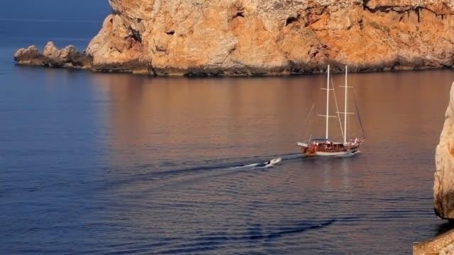 ws ha sailing boat crossing sea, limestone cliffs of capo caccia in background / sardinia, italy - sardinien stock-videos und b-roll-filmmaterial