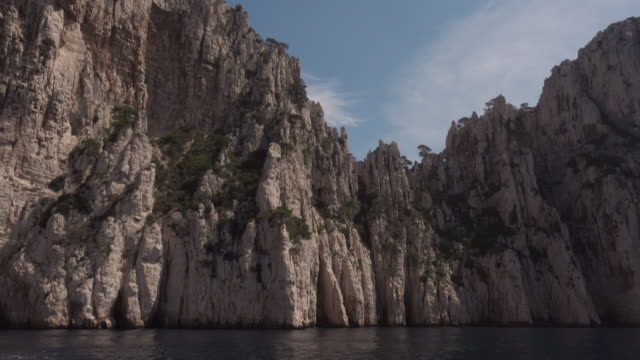 a sailing boat in front of a calanque (limestone cliffs) near cassis - limestone stock videos and b-roll footage
