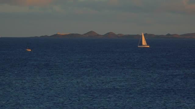 sailing boat near playa blanca, lanzarote, canary islands, spain, atlantic, europe - セーリング点の映像素材/bロール
