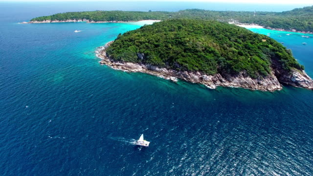 a sailing boat travels along the coast of ko racha island thailand. - david ewing stock-videos und b-roll-filmmaterial