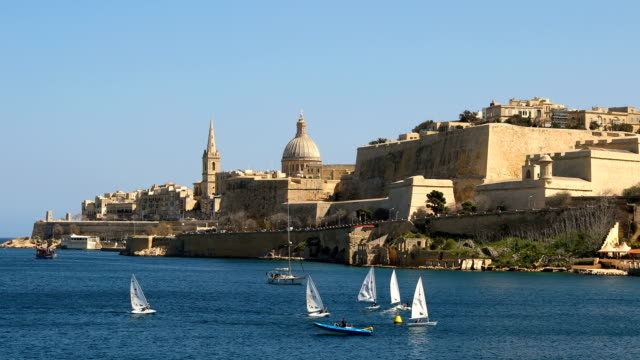 stockvideo's en b-roll-footage met sailing boats in the harbor beneath the cathedral and city walls on march 11 2018 in valletta malta valletta malta's capital has been declared the... - valletta