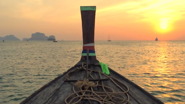 Sailing on a long tail boat during sunset in Krabi, Thailand