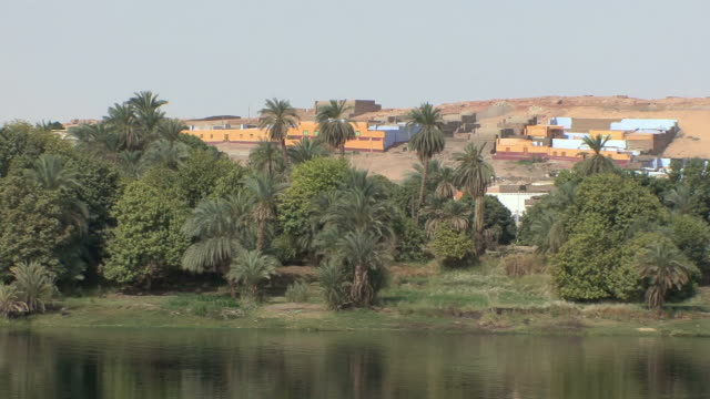 POV Sailing on Nile along Nubian village with multicolored houses, Aswan, Egypt