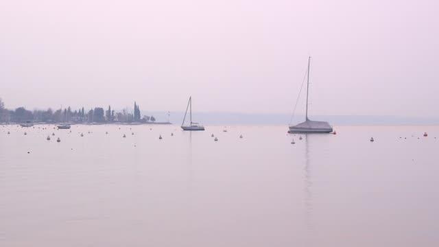 sailing ships at lake garda at dawn, garda, lake garda, lago di garda, veneto, italy - lago stock videos & royalty-free footage
