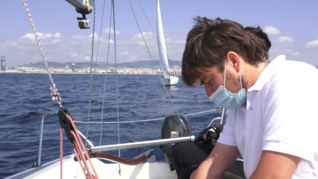 sailing teacher martin cabrera gives instructions to participant helga as helmswoman wears a face mask on board a boat where three has been a... - participant stock videos & royalty-free footage