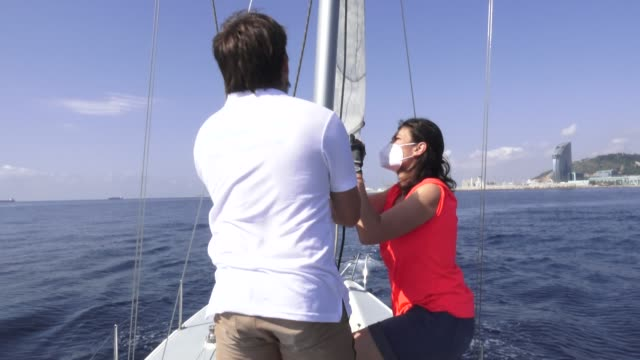 sailing teacher martin cabrera helps participant nunzia matto to hoist the mainsail wearing face masks on board a boat where three has been a... - participant stock videos & royalty-free footage