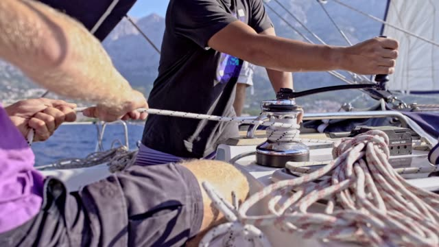 4K Sailing team adjusting crank and rigging on sunny sailboat, real time
