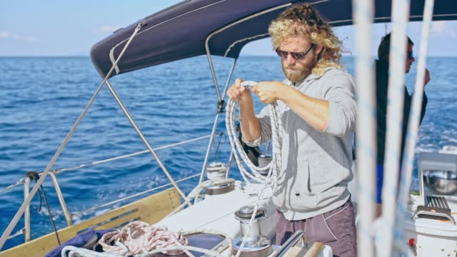 4k sailing team adjusting rigging on sunny sailboat, real time - mast sailing stock videos & royalty-free footage