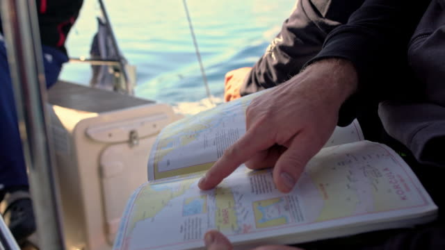 4K Sailing team checking navigational maps, real time
