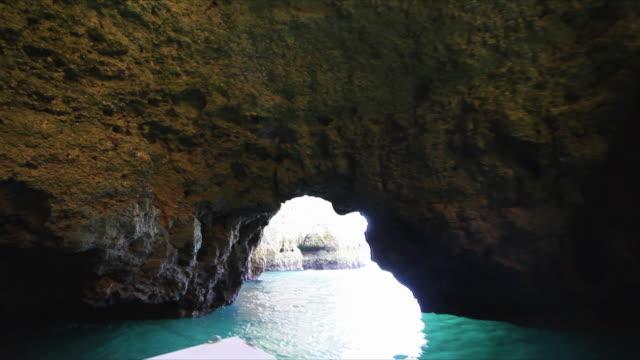 pov sailing through rocky caves and cliffs at praia dona ana, atlantic ocean coast / portugal - algarve stock-videos und b-roll-filmmaterial