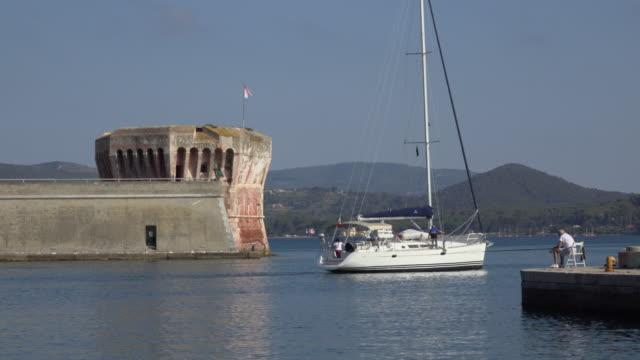 Sailing yacht leaving harbor of Portoferraio with Torre del Martello