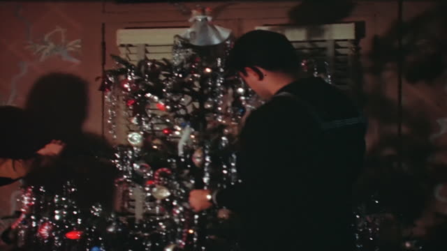 a sailor and a woman decorate a 1950's christmas tree. - 1950 stock videos & royalty-free footage