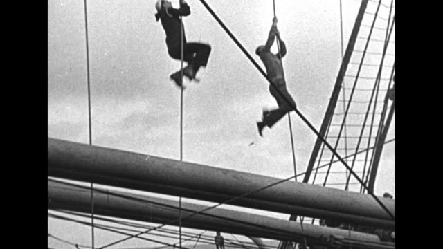 qs sailor climbs down ship rigging / three sailors and a soldier race climbing up and down ropes / soldiers and sailors look on as some of their... - schiffsmast stock-videos und b-roll-filmmaterial