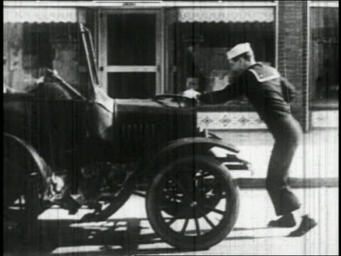 B/W 1927 sailor (Bill Blaisdell) cranking car / smoke emerges + it drives off / feature