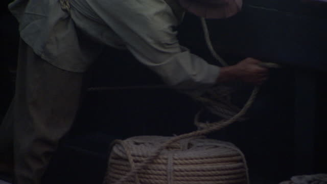 a sailor handles ropes at the side of a ship. - periodo medievale video stock e b–roll
