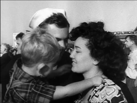 vidéos et rushes de b/w 1945 sailor hugging wife holding frightened child / ww ii homecoming / documentary - marinière