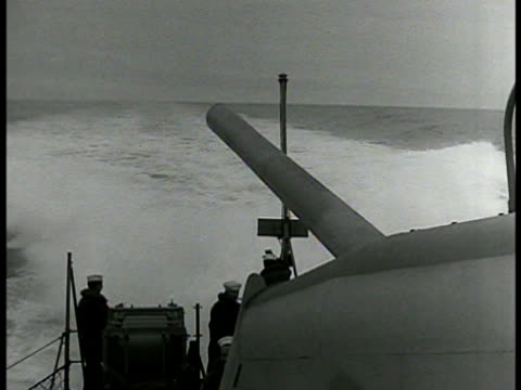 vidéos et rushes de sailor looking through crosshair ring sight ms cannon barrel rotating wake of ship bg ms depth charge exploding in water ms sailor looking w/... - 1942