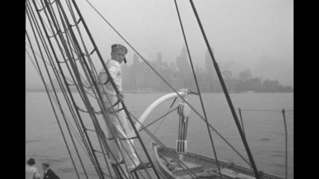 Sailor on sail's rigging of Norwegian training tall ship 'Christian Radich' waves cap at Manhattan skyline / single sailor descends rope ladder...
