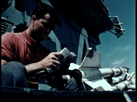 sailor reading a letter on deck of a ship missiles stacked in the background / united states - correspondence stock videos & royalty-free footage