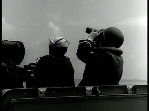 vídeos y material grabado en eventos de stock de sailor signaling blinker light. sailors on deck one w/ binoculars looking up at sky. aerial: fighter airplane diving. man w/ binoculars watching.... - avión militar