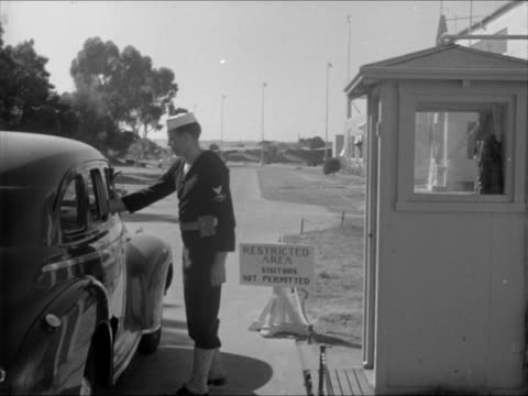vidéos et rushes de sailor standing guard at guard gate w/ airplane bg same guard clearing car to enter base pearl harbor navy yard sailors torpedo on dolly moving past... - 1941
