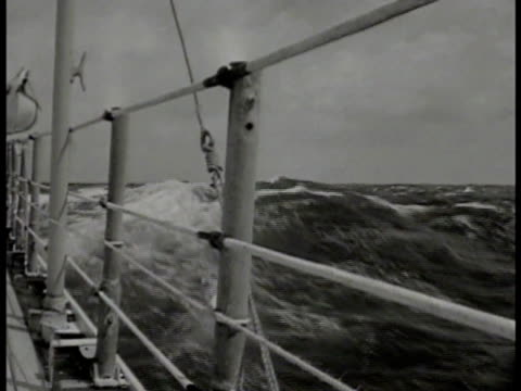 sailor standing on deck watching ship in fog next to them. ship's railing w/ swelling ocean waves beyond. vs merchant marines: eating meal at long... - marinaio video stock e b–roll