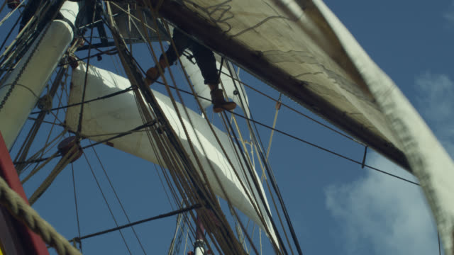 sailor unfurls sail on tall ship under sail, grenada - schiffsmast stock-videos und b-roll-filmmaterial