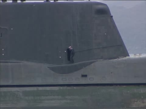sailor walks on deck of the most advanced british nuclear submarine hms astute whilst stuck on a shingle bank during sea trials - isole ebridi video stock e b–roll