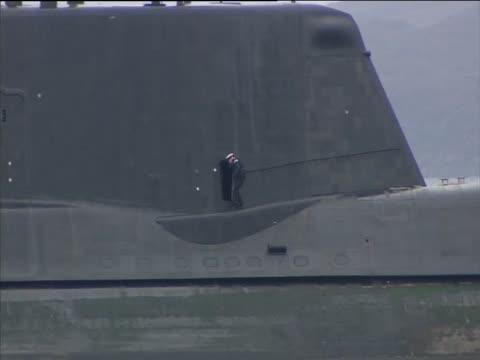 vidéos et rushes de sailor walks on deck of the most advanced british nuclear submarine hms astute whilst stuck on a shingle bank during sea trials - îles hébrides