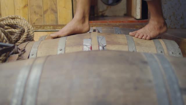 vídeos de stock, filmes e b-roll de sailor walks over barrels in hold of ship, grenada - barril