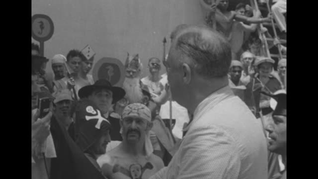 sailor with moustache and goatee and five pointed star on his cap and star painted on his t-shirt, other sailors stand behind him with stars on their... - montevideo stock-videos und b-roll-filmmaterial