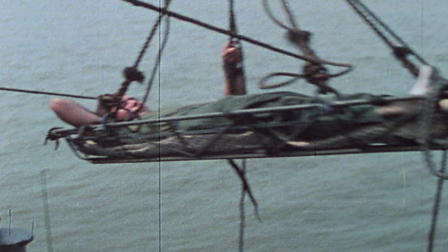 sailors aboard uss harnett county hoisting wounded casualties aboard and carrying them below in the mekong delta / vietnam - hoisting stock videos & royalty-free footage